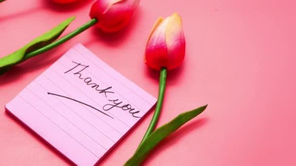 Dankeschön-Nachricht auf Haftnotiz mit Tulpenblume auf rosa Hintergrund