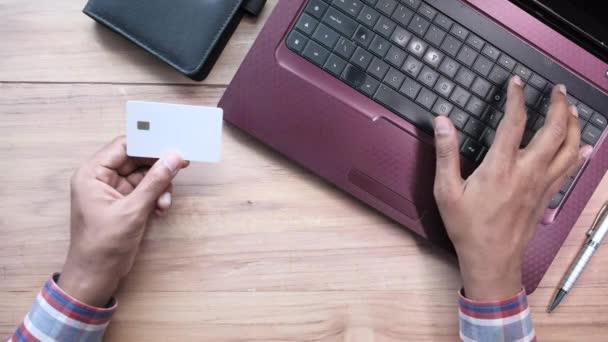 Mann hält Kreditkarte in der Hand und nutzt Laptop-Shopping online