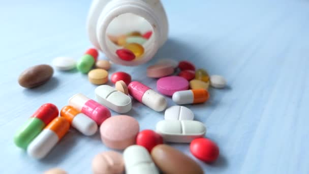 Close up of colorful pills spilling from a container