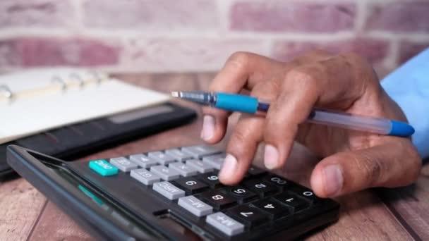 Close up of man hand using calculator
