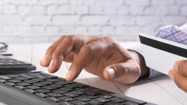 férfi kéz gazdaság hitelkártya és a billentyűzet online vásárlás