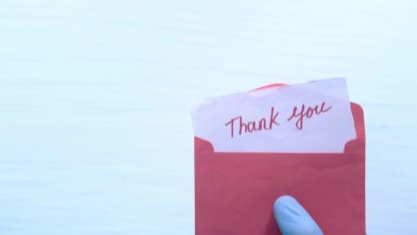 Hand in Schutzhandschuhen mit Dankesbotschaft