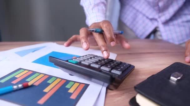close up of businessman using calculator on office desk