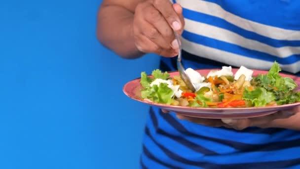 junger Mann in lässiger Kleidung isst frischen Salat, gesundes Ernährungskonzept
