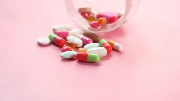 Close up of many colorful pills and capsules spilling on pink background
