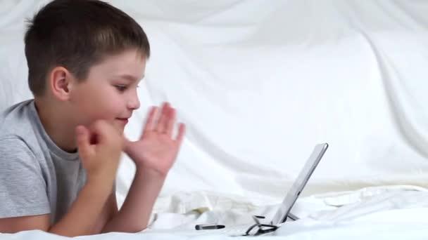 A srác digitális táblagépet használ, egyedül fekszik az ágyon. A gyerek iskolai házi feladatot csinál, jegyzetel a másolóban. E tanulás, távoktatás, oktatás online tanárokkal az otthoni karanténban.