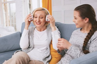 Happy mature woman wearing headphones