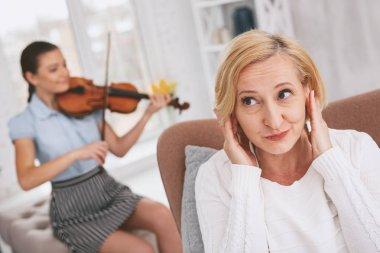 Joyful blonde female putting hands on ears