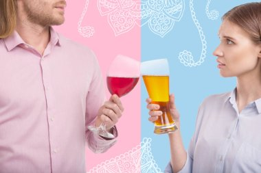 Young couple clanging glasses while drinking alcohol