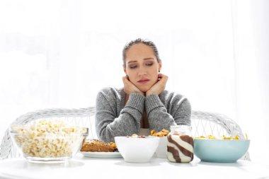 Gloomy bleak woman selecting food