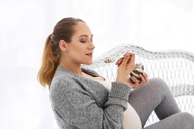 Happy pregnant woman enjoying cocoa spread