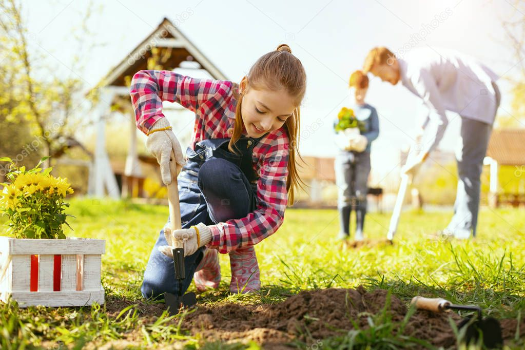 Joyful positive girl looking at the ground while planting flowers there