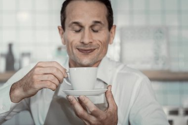 Cheerful waiter trying new sort of coffee