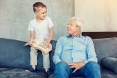 Fotografie Ziemlich senior Mann sah den jungen mit einem großen Buch