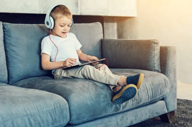 Cute boy in big headphones playing the games