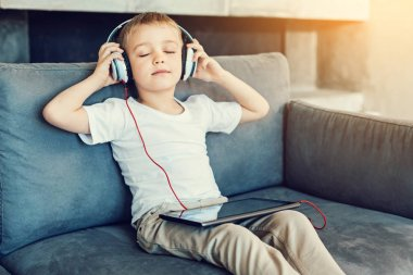 Relaxation. Pleasant little relaxed child sitting with his eyes closed while listening to the calm music