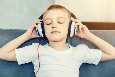 Cute relaxed boy in big white headphones