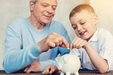 Concentrated relatives putting a coin into a moneybox