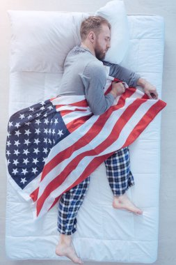 Young man falling asleep with usa flag in hands