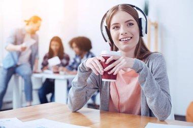 Positive delighted female listening music