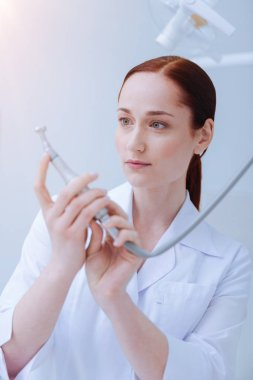 Portrait of serious dentist that examining her equipment