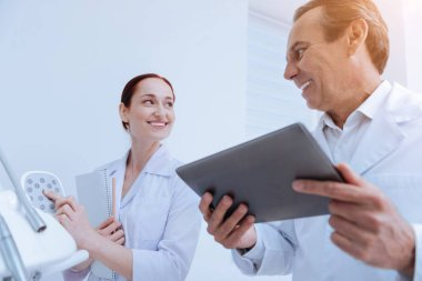 Mature doctor holding his gadget in both hands