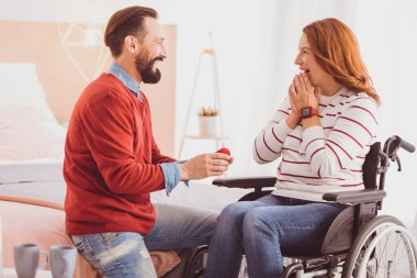 Joyful brunette man proposing marriage to his girlfriend
