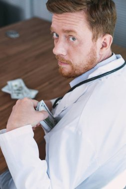 Concentrated wicked doctor taking money