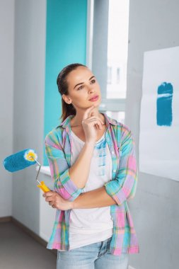 Meditative woman holding a roller to paint the walls