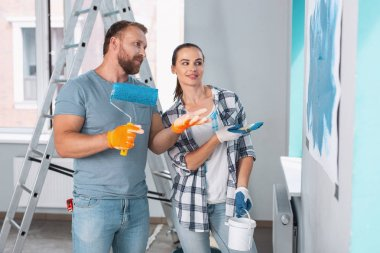 Happy painters discussing painting walls