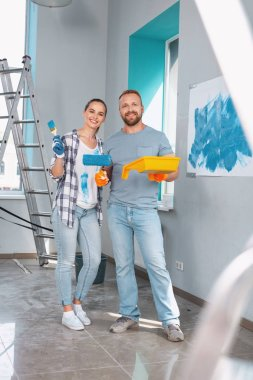 Joyful skilled painters standing together