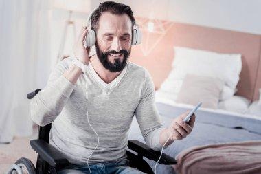 Cheerful crippled man listening to music