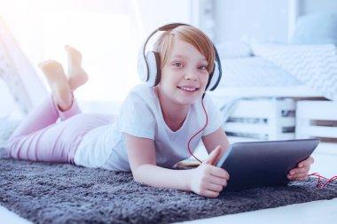 Joyful girl with headphones smiling into camera