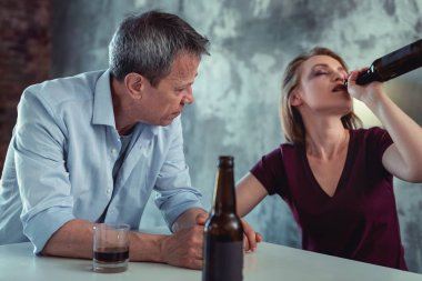 White collar worker feeling concerned looking at drunk wife