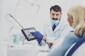 Fotografie Fröhliche Zahnarzt demonstriert seine gadget