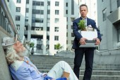 Fired man leaving office seeing homeless man