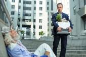 Fotografie Fired man leaving office seeing homeless man
