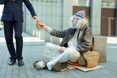 Street person sitting on the street begging for help