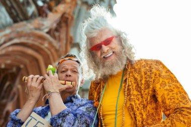 Beaming smiling hippies wearing bright stylish shirts