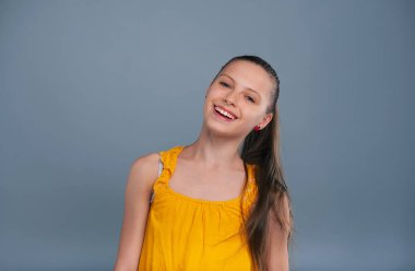 Cheerful teenage girl tilting her head and smiling
