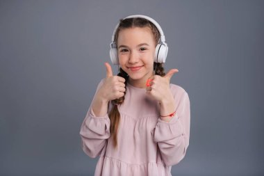Cute teenage girl listening to music and showing thumbs-up