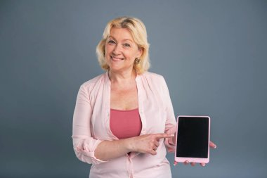 Beautiful middle-aged woman promoting a tablet
