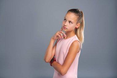 Petite teenage girl contemplating something