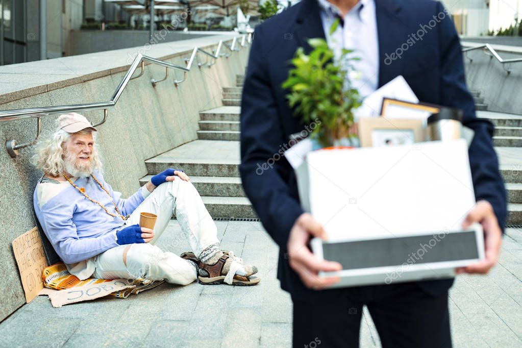 Homeless beggar looking at fired sad man