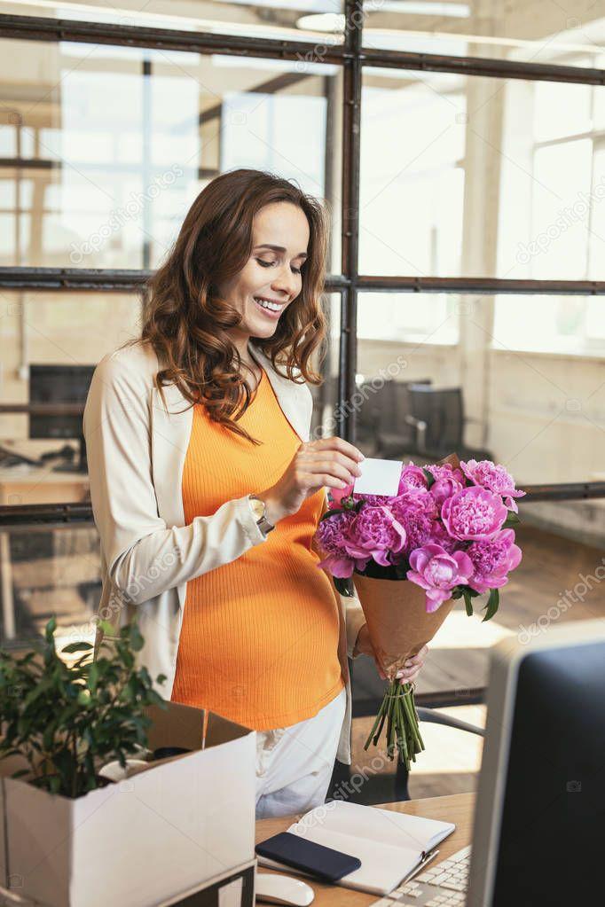 Happy pregnant employee receiving present