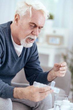 Thoughtful senior man consuming drug