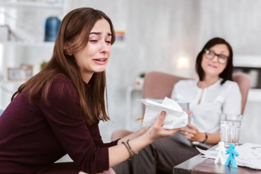 Emotional woman crying while a psychologist looking at her