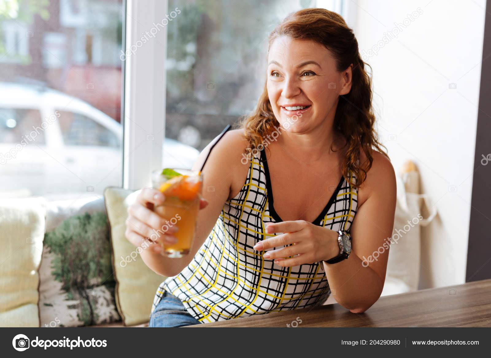 b504e089b5cc Κοκκινομάλλης γυναίκα ακτινοβολούν φορώντας κομψά πολύχρωμα μπλούζα  πίνοντας κοκτέιλ στο εστιατόριο — Εικόνα από ...