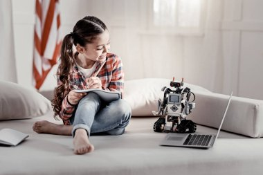 Busy cute girl drawing robot on the couch