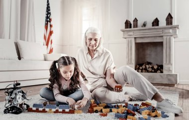 Relaxed happy granny helping granddaughter with lego